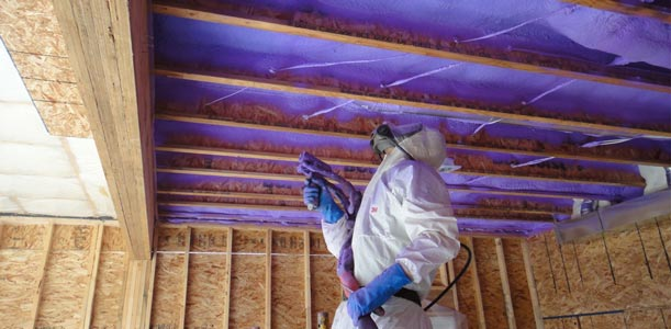 person spraying spray foam insulation into a ceiling